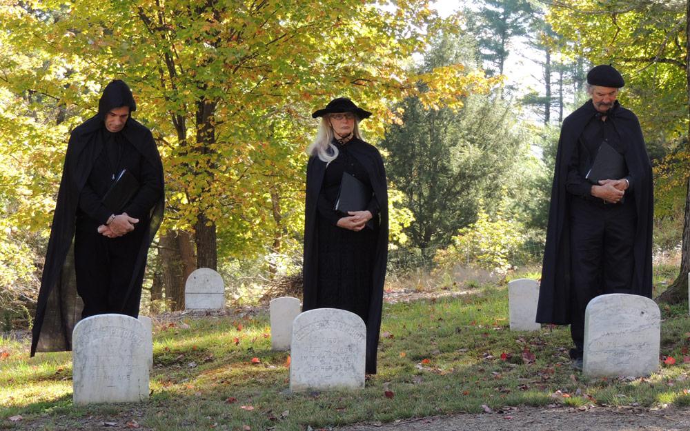 three dramatic readers behind headstones